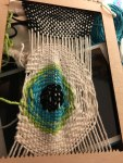 a funny eyeball in space woven from yarn into a tapestry. Almost done!